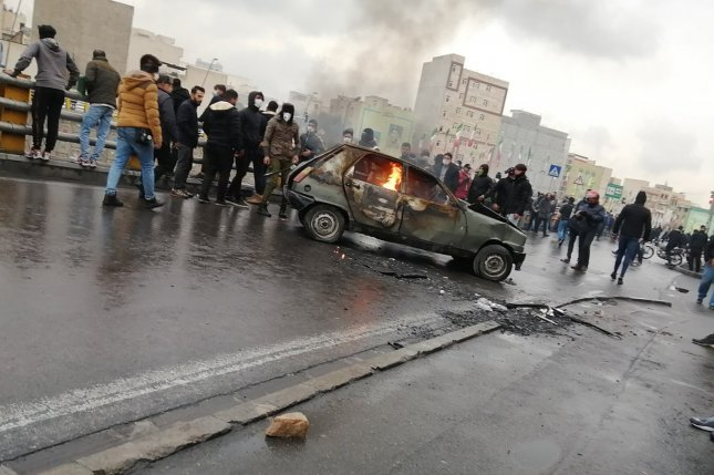 Iranian demonstrators stand near a burning vehicle amid clashes with police over a sudden spike in fuel prices, in Tehran, Iran, on November 16, 2019. File Photo by EPA-EFE