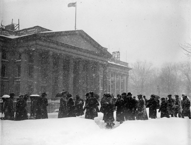 Pedestrians make their way through the streets of Washington, D.C. during a fierce snowstorm in late January 1922. File Photo by Library of Congress/UPI