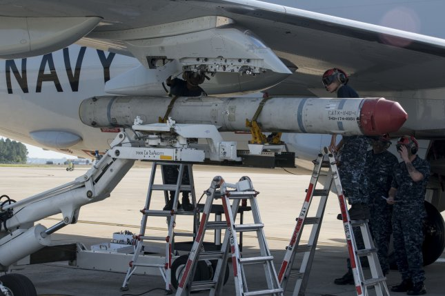 Two aviation ordnancemen load an AGM-84K SLAM-ER missile on a P-8A Poseidon at Naval Air Station Jacksonville in Florida in April 2014. Photo by Jason Kofonow/U.S. Navy