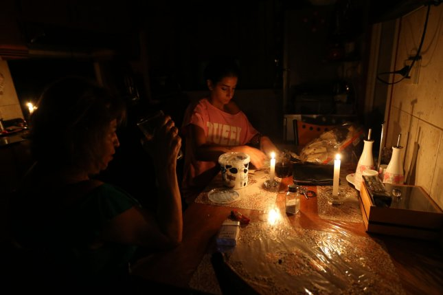A woman prepares dinner in her kitchen at candlelight in Beirut, Lebanon, on September 11 amid regular power outages. Most of the country was without power Saturday due to fuel shortages. Photo by Nabil Mounzer/EPA-EFE