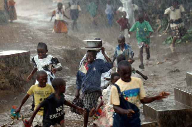Children run in the rain in the town of Bunia, Democratic Republic of Congo. A new lawsuit accuses several U.S. tech companies of failing to prevent injury and death to children in the mining of cobalt. File Photo by Maurizio Gambarini/EPA