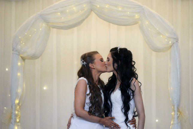 Robyn Peoples (L) and Sharni Edwards kiss during their wedding in Carrickfergus, Northern Ireland, on Tuesday. They were the first same-sex couple to marry after a ban was lifted last fall. Photo by Mark Marlow/EPA-EFE