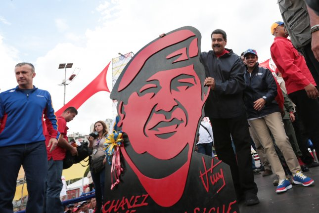 Venezuelan President Nicolas Maduro (R) holds an image depicting former President Hugo Chavez next to his wife Cilia Flores during a demonstration in Caracas. The Trump administration on Tuesday said all options are on the table when it comes to sanctions on Venezuela in reaction to Maduro's attempts to rewrite the Constitution. File Photo by Mira Flores/EPA/Handout