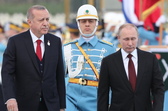 Turkish President Recep Tayyip Erdogan (L) and Russian President Vladimir Putin (R) review honor guards during a welcoming ceremony at the Presidential Palace in Ankara on Thursday. Foreign Minister Mevlut Cavusoglu said Sunday if the United States approves a proposed law that would halt weapons sales to Turkey, the nation will retaliate. Photo by Tolga Bozoglu/EPA