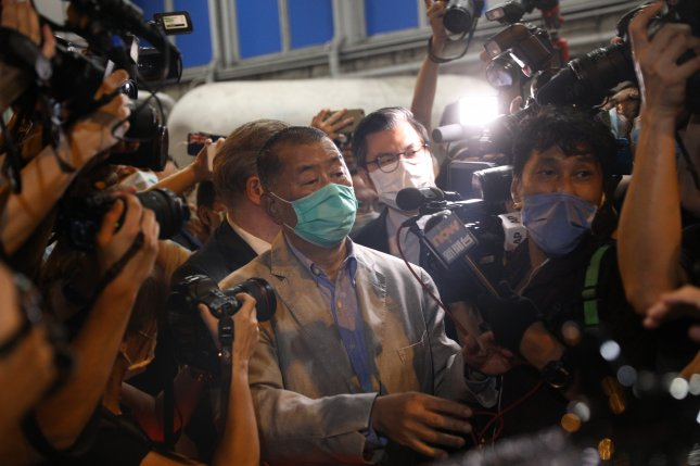 Hong Kong media tycoon and founder of Apple Daily, Jimmy Lai (C) is surrounded by members of the media as he leaves a police station after he was released on bail in Hong Kong, China before returning to his office after midnight, Wednesday. File Photo by Jerome Favre/EPA-EFE