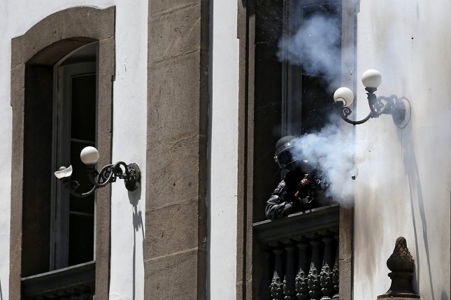 Protesters clashed with police during a demonstration against cuts in the Rio de Janeiro state budget in Brazil on Tuesday. Officers were seen firing rubber bullets at protesters from within a historic church. The chief of Brazil's Military Police apologized for the incident. Photo by Marcelo Sayao/European Pressphoto Agency