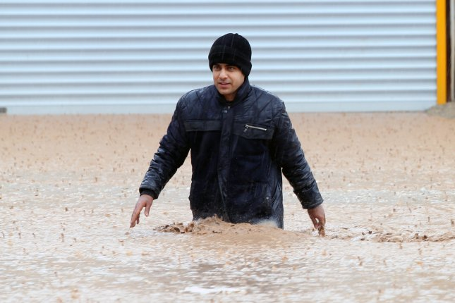 An Iranian man crosses a flooded street in the city of Khorramabad, Lorestan Province, western Iran, on Monday. Photo by Saeed Soroush/EPA