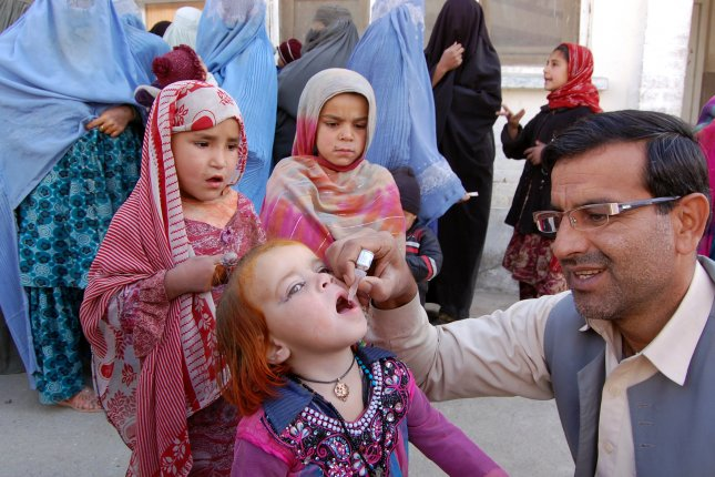 A health worker administers a vaccine to a child at civil hospital in Chaman, Pakistan. Experts said Tuesday almost 20 million children went unvaccinated last year. File Photo by Matiullah Achakzai