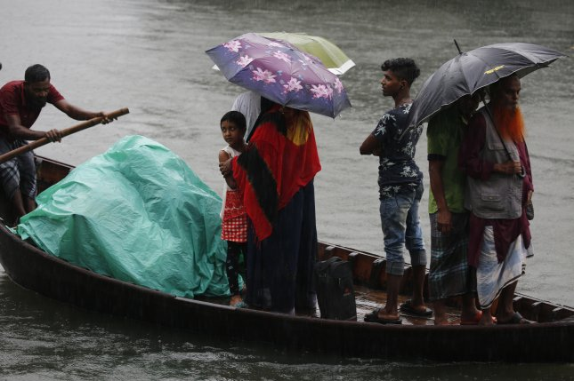 Bangladeshi passengers cover themselves with a plastic sheet and umbrellas as they cross the Buriganga River by boat during Cyclone Bulbul in Dhaka, Bangladesh, on Saturday. Photo by Monirul Alam/EPA-EFE