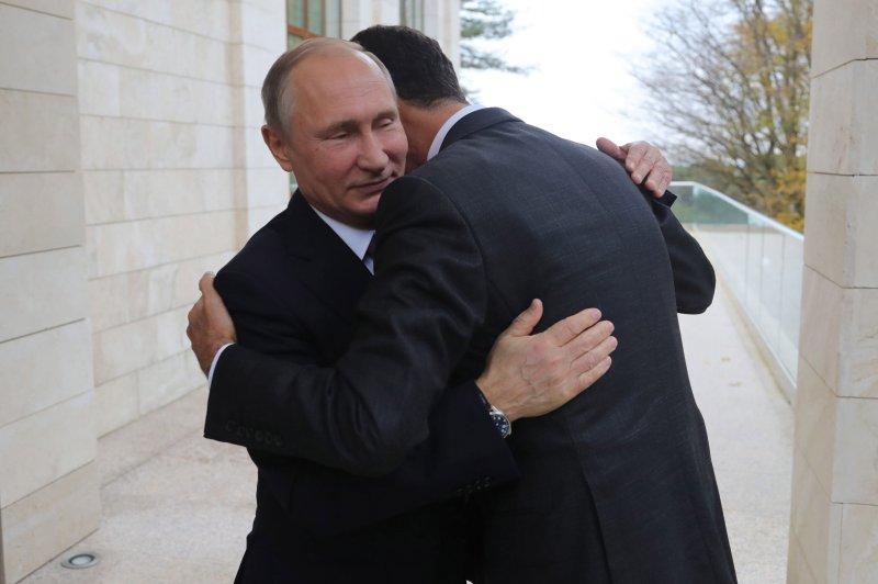Russian President Vladimir Putin embraces Syrian President Bashar al-Assad during a meeting in Sochi, Russia, on Monday -- a visit that was unscheduled. Photo by Michael Klimentyev/EPA-EFE/Sputnik/Kremlin/Pool