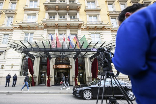 Austrian police officers and a journalist stand in front of a hotel on the day of a Joint Comprehensive Plan of Action Joint Commission meeting in Vienna on April 6. Photo by Christian Bruna/EPA-EFE