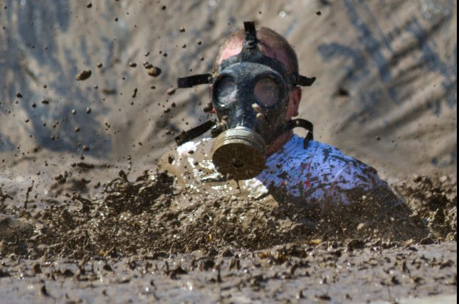 This participant wearing a gas mask during a mud run in Boise, Idaho, might not have to worry about getting sick from ingesting feces-contaminated mud. Some 1,000 participants in a run in France were sickened with norovirus after likely ingesting the virus from muddy water. Photo by txking/Shutterstock