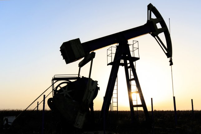 Oil and gas well pump jack in a rural field at sunset. File Photo by ekina/Shutterstock