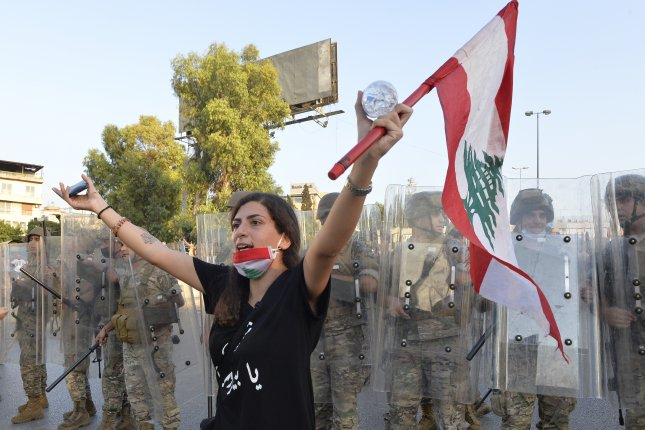 An anti-government protester carries a national flag as she shouts slogans in front of the Lebanese army soldiers during a protest on the road leading to the presidential palace in Baabda, east Beirut, Lebanon, last Saturday. Photo by Wael Hamzeh/EPA-EFE