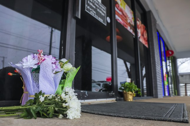 Flowers left by well-wishers sit at the entrance to Young's Asian Massage spa in Acworth, Ga., where Robert Aaron Long, was charged with four counts of murder and one count of aggravated assault for shooting and killing eight people at the spa and two others in the Atlanat area. Photo by Erik S. Lesser/EPA-EFE