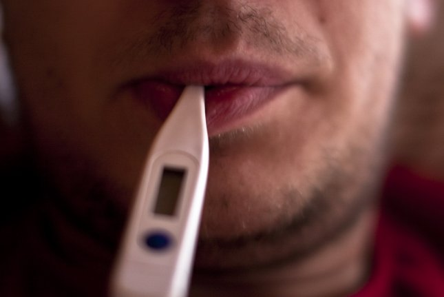 A sick man takes his temperature. Photo by Claus Rebler/Flickr
