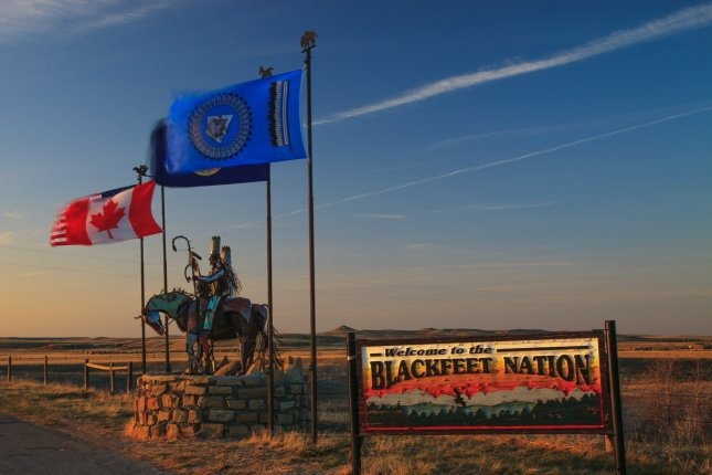 Native Americans in Montana are more likely than White people there to catch or die from COVID-19, though Blackfeet Nation in the northern part of the state -- the entrance to the Blackfeet Tribal Reservation is pictured -- saw its illness and death rates decline after instituting mask wearing and social distancing. Photo by Murray Foubister/Wikimedia Commons