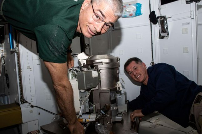 Astronauts Mark Vande Hei (L) and Shane Kimbrough install a new space toilet aboard the International Space Station on May 24. Photo courtesy of NASA