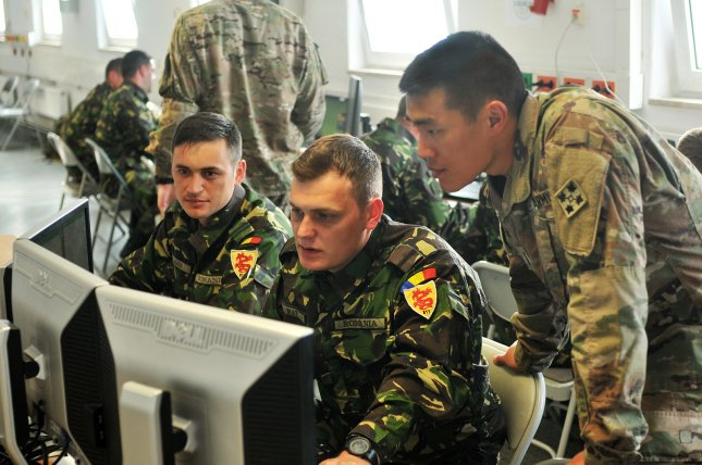 From left, Romanian army 1st Lt. Sergio Gligor, an operations officer, and 2nd Lt. Andrei Ma, a battle captain, both with the 811th Infantry Battalion, and U.S. Army 1st Lt. Jeff Yao, a military intelligence officer with the 3rd Armored Brigade Combat Team, 4th Infantry Division, track a counterattack in a simulated fight against a conventional force during a command-post exercise conducted at Grafenwoehr Training Area, Germany, on May 16, 2017. Army photo by Capt. Scott Walters