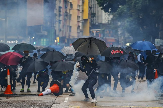 A taxi driver rammed a group of pro-democracy demonstrators and police fired tear gas at protesters during demonstrations in Hong Kong on Sunday. Photo by Fazry Ismail/EPA