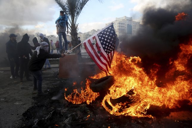 A Palestinian protester burns the flag of the United States during clashes with Israeli soldiers following a protest in the west Bank city Ramallah, on December 7, 2017. A survey ranking the Best Countries in the world Tuesday cited growing unpopularity with the Trump administration. Photo by Shadi Hatem/EPA-EFE