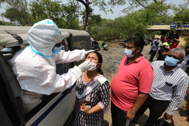 A health worker administers a swab test at a roadside coronavirus checkpoint in Bhopal, India, on April 10. Photo by Sanjeev Gupta/EPA-EFE