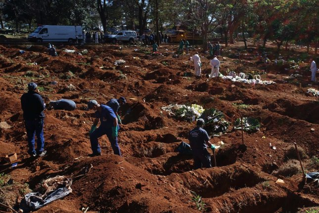 Workers bury victims of the COVID-19 pandemic Tuesday in the Vila Formosa cemetery in Sao Paulo, Brazil, the largest cemetery in Latin America. Photo by Paulo Whitaker/EPA-EFE
