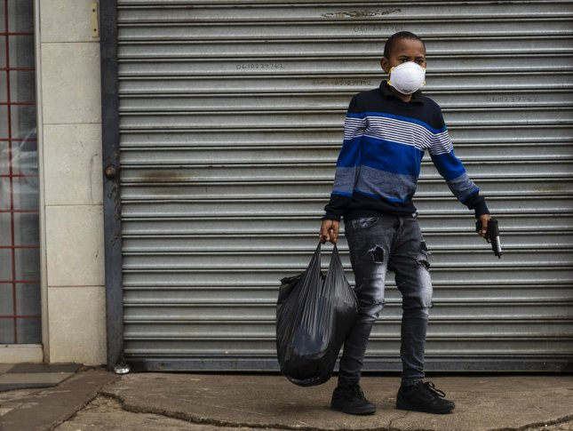 A young boy carries a bag of groceries in one hand and a toy gun in another in Johannesburg, South Africa, on April 8. Photo by Kim Ludbrook/EPA-EFE