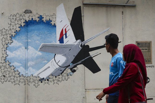 People look at a mural depicting puzzle pieces and the tail section of Malaysia Airlines flight MH370 at Shah Alam, outside Kuala Lumpur, Malaysia, on Thursday. Photo by Fazry Ismail/EPA-EFE