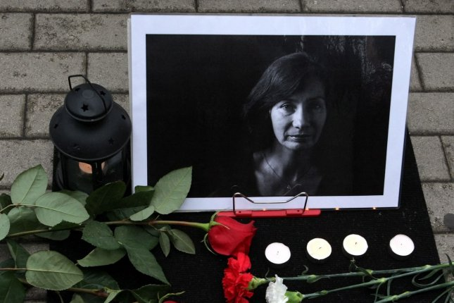 Flowers are seen with a photo of journalist and human rights activist Natalya Estemirova in Moscow, Russia, on August 24, 2009, about a month after she was found dead. File Photo by Maxim Shipenkov/EPA
