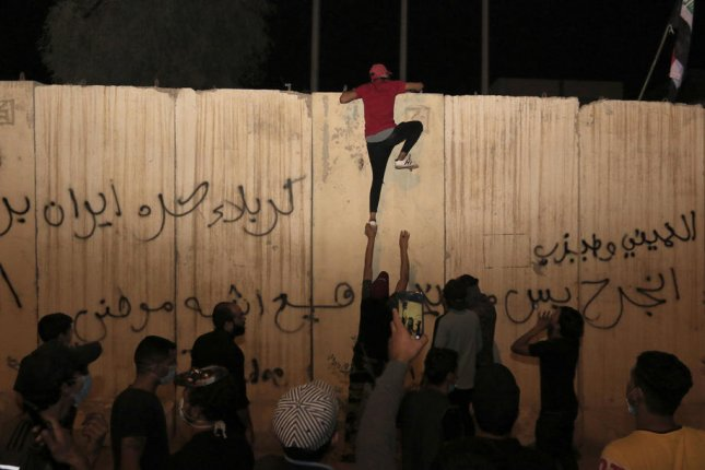 An Iraqi protester climbs the concrete wall of the Iranian consulate in Karbala, Iraq, on Sunday.  Photo by Furqan al-Aaraji/EPA-EFE