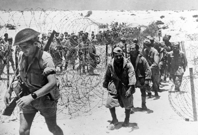 Italian prisoners of war captured in the El Alamein area entering the cage preceeded by their guard. Picture taken ca. Nov. 1942. File Photo by OWI/UPI