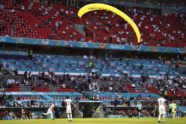 A protester parachutes into Allianz Arena before a UEFA EURO 2020 Group F soccer match between France and Germany on Tuesday in Munich, Germany. Photo by Lukas Barth-Tuttas/EPA-EFE
