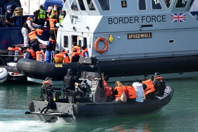 A boat carrying migrants wait to disembark at a port in Dover, Britain, on Thursday. Hundreds of refugees from Syria and other nations experiencing unrest have arrived by crossing the English Channel for 10 straight days, officials said. Photo by Andy Rain/EPA-EFE