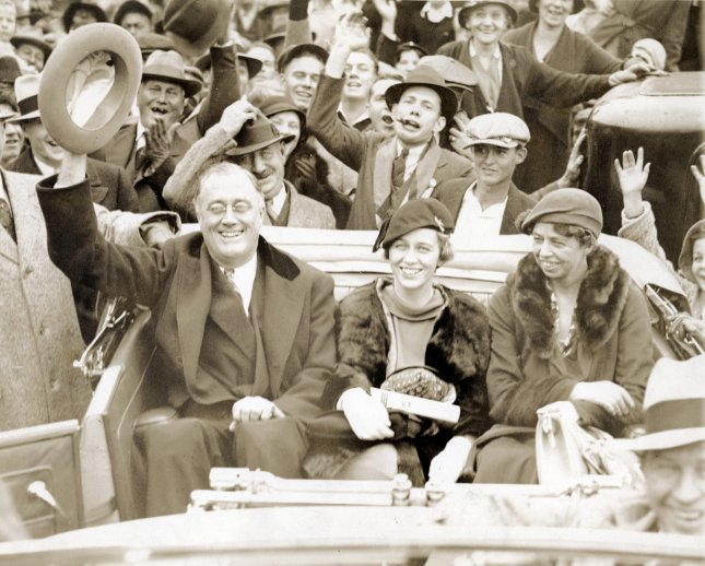 New York Gov. Franklin Delano Roosevelt riding in the back of an open top car with his daughter Anna Roosevelt Halsted and wife Eleanor while campaigning in Warm Springs, Ga., on October 24, 1932. The trio were met by massive crowds while traveling en route from their cottage to the train station. File Photo courtesy FDR Presidential Library