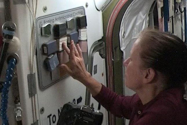 NASA astronaut Shannon Walker touches antimicrobial surface coatings on various surfaces as part of a test for Boeing aboard the International Space Station. Photo courtesy of NASA