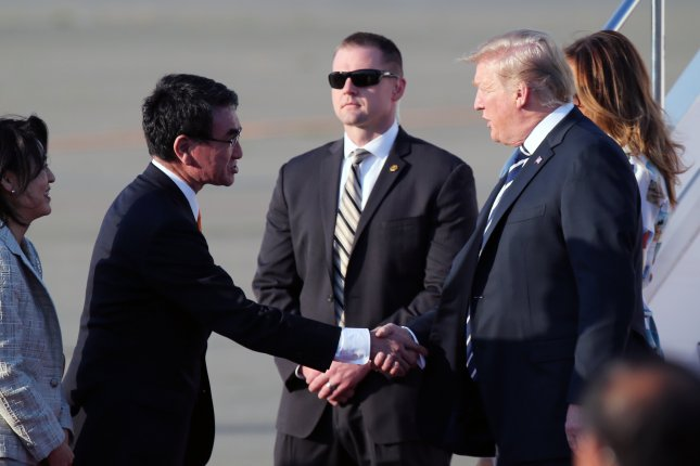 President Donald Trump shakes hands with Japanese Foreign Minister Taro Kono upon his arrival with first lady Melania at Haneda International Airport in Tokyo on Saturday. Photo by Koji Sasahara/pool/EPA