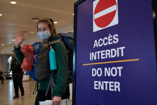 A woman with a mask arrives from the U.S. at the Montreal-Pierre Elliott Trudeau International Airport in Montreal, Canada, on March 16, 2020. Canada and the U.S. have had a travel ban for nonessential travel for one year but traveling by air is exempted though negative tests and quarantine are required. Citizens or permanent residents of the country they are entering are also exempted from the ban. Photo by Andre Pichette/EPA-EFE