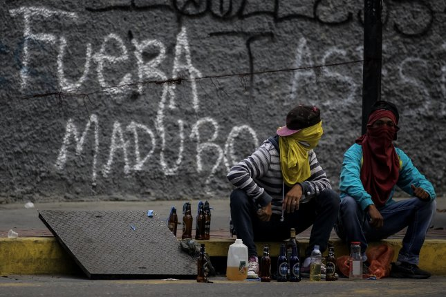 Demonstrators on the streets of Caracas sit during a protest amid a 48-hour general strike against President Nicolas Maduro's Constituent Assembly on Wednesday. Photo by Miguel Gutierrez/EPA