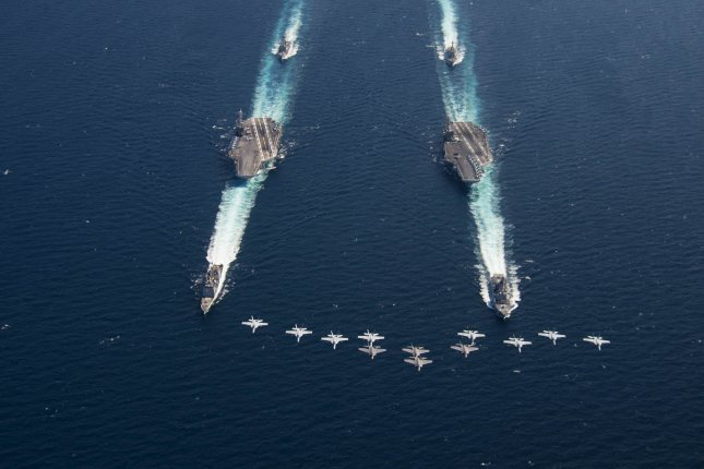 Aircraft from the Freedom Fighters of Carrier Air Wing 7 fly in formation above the Nimitz-class aircraft carriers USS Abraham Lincoln and USS Harry S. Truman, the Arleigh Burke-class guided-missile destroyer USS Mason from Destroyer Squadron 2, the Arleigh Burke-class guided-missile destroyers USS Forrest Sherman and USS Arleigh Burke from Destroyer Squadron 28, and the Ticonderoga-class guided-missile cruiser USS Normandy while transiting the Atlantic Ocean. Photo by Mass Communication Specialist 1st Class Brian M. Brooks/U.S. Navy