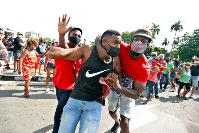 An anti-government protester is arrested during a pro-government rally in Havana on Sunday. Photo by Ernesto Mastrascusa/EPA-EFE