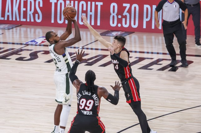 Milwaukee Bucks forward Khris Middleton (L) makes a 3-point shot over Miami Heat defenders Jae Crowder (C) and Tyler Herro (R) during overtime in Game 4 of their Eastern Conference semifinal series Sunday at the ESPN Wide World of Sports Complex near Orlando, Fla. Photo by Erik S. Lesser/EPA-EFE