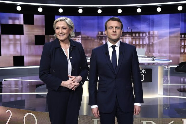 French presidential candidates Marine Le Pen (L) of the far-right Front National Party and Emmanuel Macron (R) of the centrist En Marche! movement pose together prior to a televised debate. Voting began Saturday, after Macron announced a computer hack to his campaign. Photo by Eric Feferberg/EPA/Pool