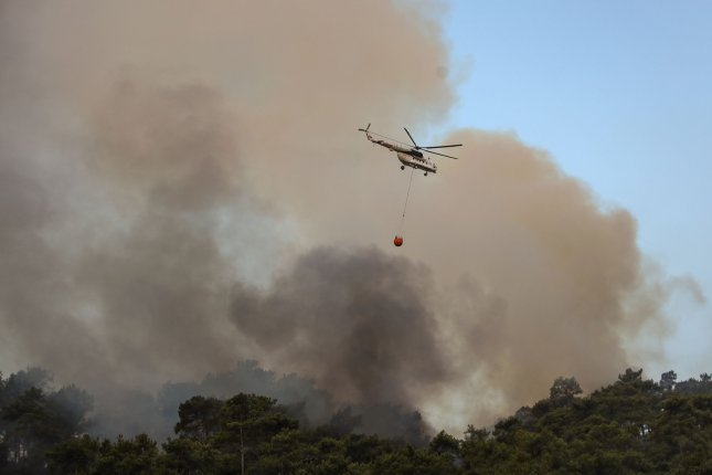 A helicopter carries water to put out a wildfire burning at a rural area of Marmaris district of Mugla, Turkey, on Saturday. Photo by Erdem Sahin/EPA-EFE