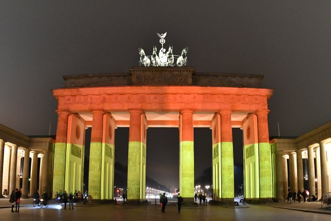 Berlin's Brandenburg Gate is illuminated in the colors of the German flag on Tuesday to commemorate the victims of the truck crash at a holiday market a day earlier. At least 12 people were killed and dozens were injured when the Polish delivery truck ran into revelers at the Breitscheidplatz market. Photo by Paul Zinken/European Pressphoto Agency