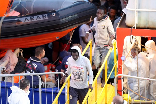 Migrants aboard the Lifeline NGO rescue vessel stranded in the Mediterranean with more than 200 migrants disembark in Valletta, Malta, on Wednesday. Photo by Domenic Aquilina/EPA-EFE