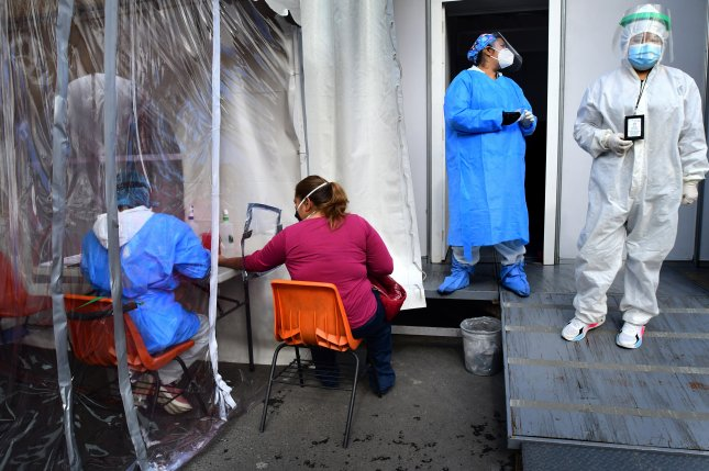 Health employees perform COVID-19 tests on people in a pavilion installed in the Central de Abastos, the largest food distributor in the entire country, in Mexico City, Mexico, on Thursday. Photo by Jorge Nunez/EPA-EFE