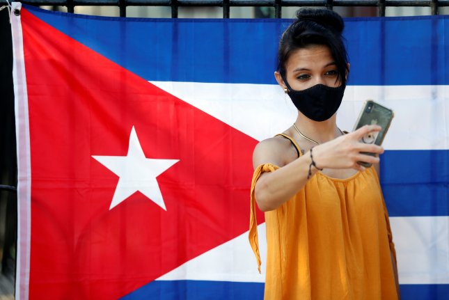 A woman poses for a photo during a concert organized by youth organizations to condemn the media campaign in support of the San Isidro movement, in Havana, Cuba, on November 29. Photo by Ernesto Mastrascusa/EPA-EFE