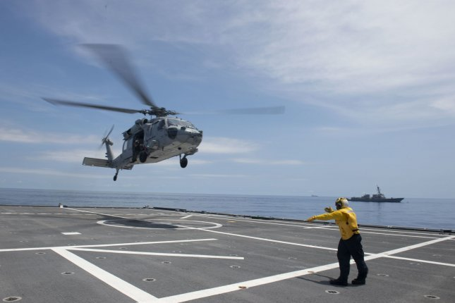 Sailors assigned to the littoral combat ship USS Tulsa and Helicopter Sea Combat Squadron 21 conduct flight operations while sailing with the guided missile destroyer USS Kidd on July 9. Photo by Mass Communication Specialist 3rd Class Chase Stephens/U.S. Navy