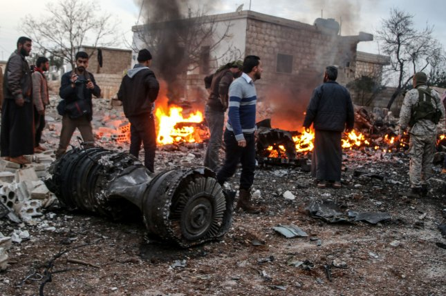 Civilians walk amid debris of a Russian military fighter jet in the eastern Idlib countryside in Syria on February 3, 2018. File Photo by Abdalla Saad/EPA-EFE